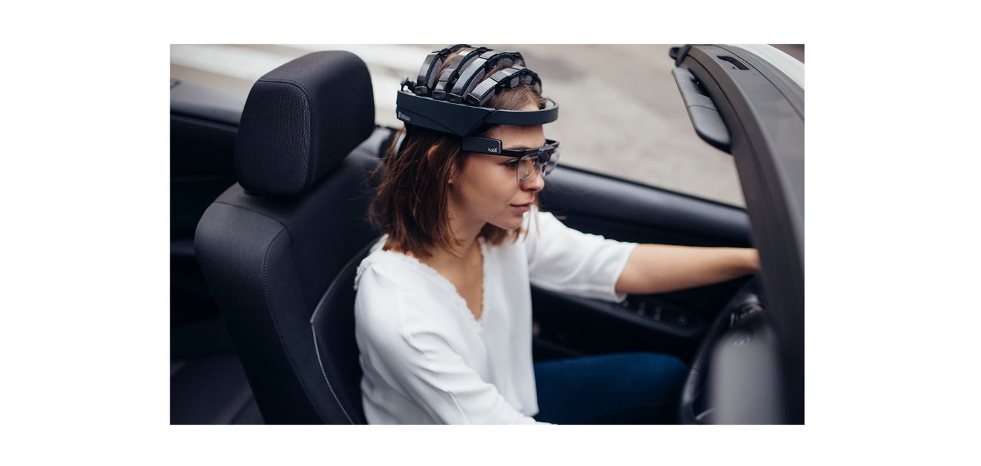 girl driving a car with a mobile and wireless eeg