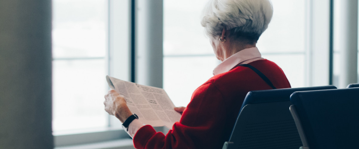 Elderly person with dementia reading a book for cognitive rehabilitation with exercises to train the brain
