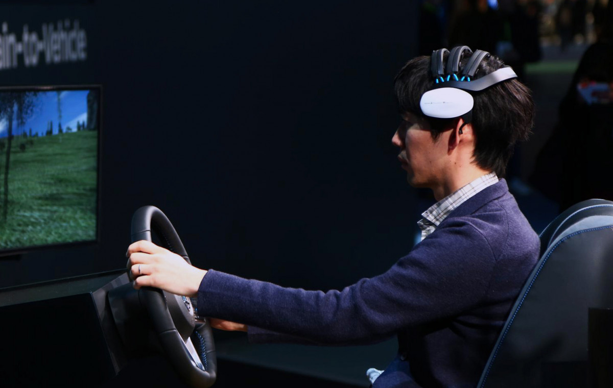 Person using a brain computer interface called brain to vehicle in a car to improve safety on the steering wheel