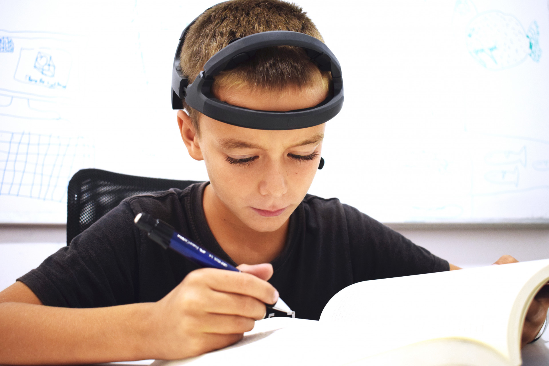 boy studying while is being monitored with an EEG